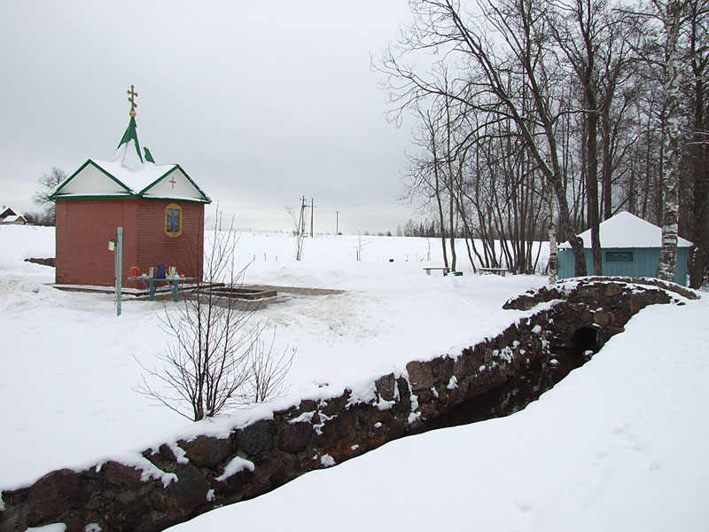 Эстония, Ида-Вирумаа, Куремяэ. Часовня Успения Пресвятой Богородицы над источником, фотография. общий вид в ландшафте, В правой части кадра за мостиком– купальня